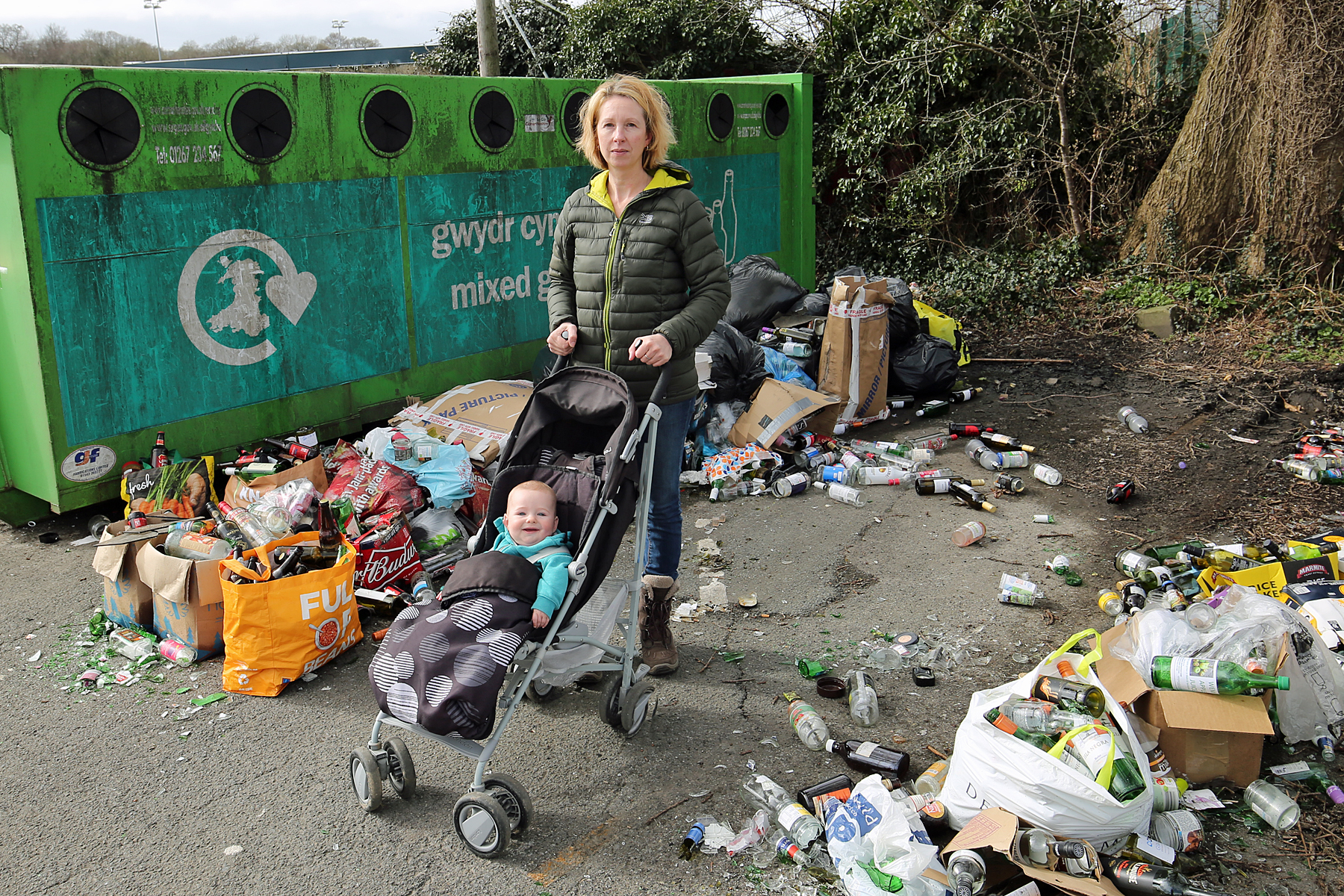 Cara Sanderson and six-month-old Jacob in the glass-strewn recycling area at Newcastle Emlyn. PICTURE: Barry Adams