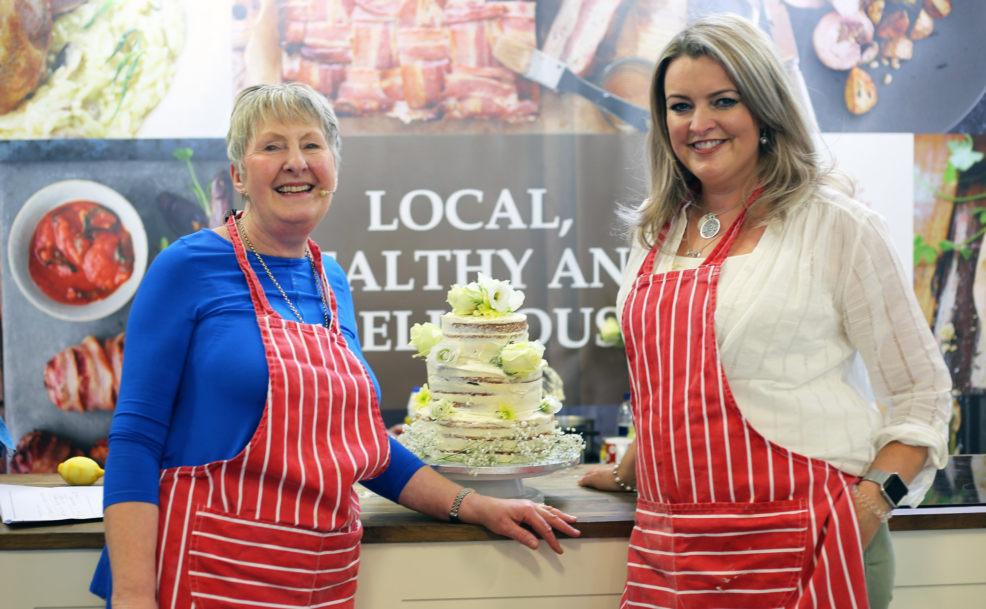 Bake Off's Val Stones and Louise Williams whip up a replica three-tiered, elderflower and lemon royal wedding cake, made with Welsh products donated by the exhibitors in the Food Hall.